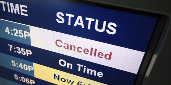 Flight cancelled notice on an airport arrival departure board sign.